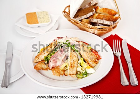 Caesar salad served on plate with bread - stock photo