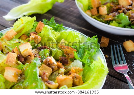 caesar salad topped with mustard dressing, beacon, and baked bread cube