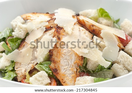 Caesar salad with cheese on white plate - stock photo