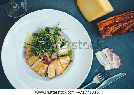 Caesar salad with chicken and greens on black table