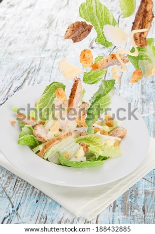 Caesar salad with chicken and greens on wooden table - stock photo