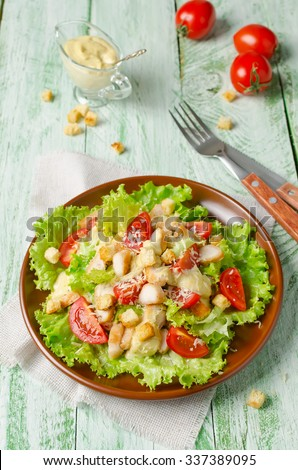 Caesar salad with chicken, croutons and greens on wooden table - stock photo