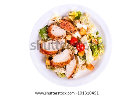 Caesar salad with chicken on a plate. On a white background. - stock photo