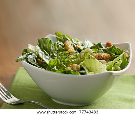 Caesar salad with copyspace on a wooden table - stock photo