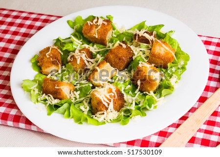 Caesar salad with croutons on a white plate
