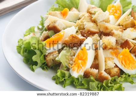 Caesar salad with eggs, lettuce, croutons, parmesan, and chicken breast - stock photo