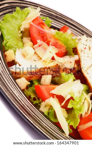 Caesar Salad with Grilled Chicken Breast, Garlic Crouton, Lettuce, Tomatoes and Grated Parmesan Cheese closeup on Striped Plate - stock photo