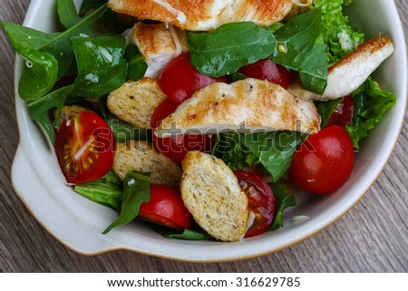 Caesar salad with grilled chicken breast on the wood background - stock photo