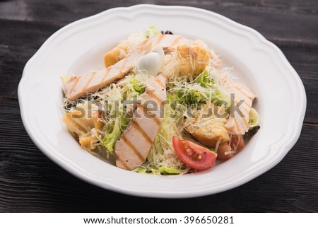 Caesar salad with grilled chicken in restaurant table