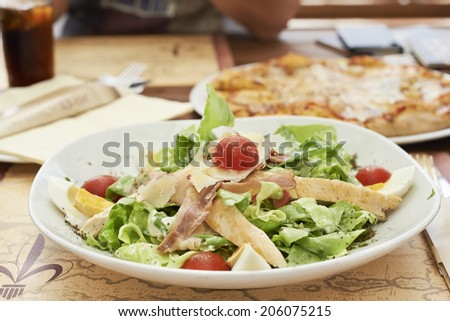 Caesar salad with grilled chicken, smoked ham, eggs and cherry tomatoes - stock photo
