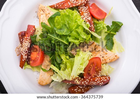 Caesar salad with grilled chicken, tomato and sesame in white dish