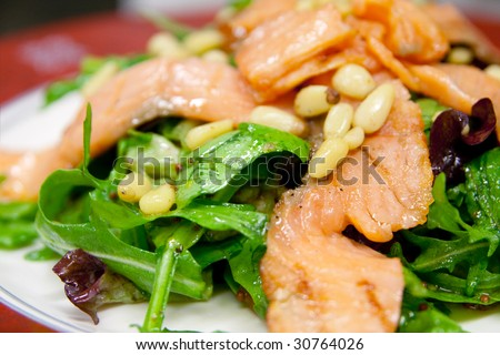 Caesar salad with salmon and pine nuts, closeup