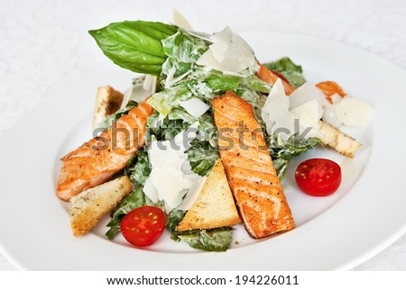 Caesar salad with salmon, cherry tomatoes, parmesan, lettuce and basil - stock photo