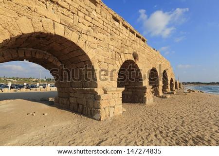 Caesarea aqueduct beach at sunset - stock photo