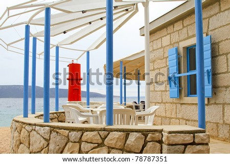 Cafe at seaside with red lighthouse tower