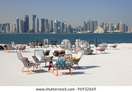 Cafe chairs with view of Doha downtown skyline, Qatar, Middle East - stock photo
