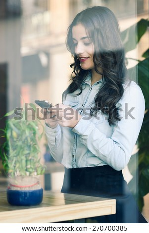 Cafe city lifestyle. Young woman sitting indoor in trendy urban cafe writing with her mobile phone. Cool young modern caucasian female model in her 20s - stock photo
