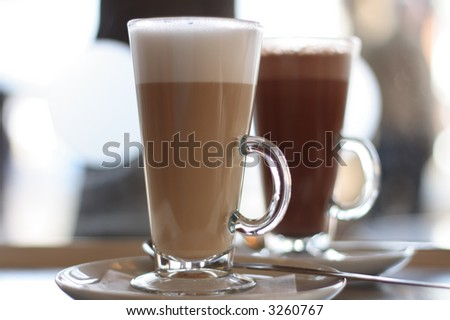 Cafe Coffee Latte in a glass with hot chocolate in background - stock photo