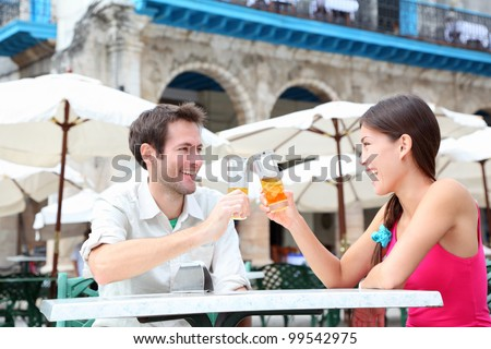 Cafe couple drinking talking having fun laughing smiling happy. Young interracial couple on travel vacation drinking rum in Old Havana, Cuba, Plaza de la Catedral. - stock photo