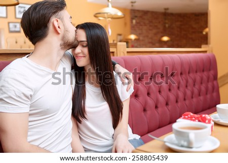Cafe dating. Shot of young couple bonding and kissing each other while sitting n the cafe with a little gift box  - stock photo