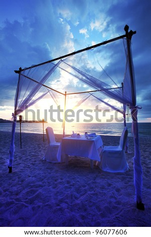 Cafe on the beach at sunset. Vertical shot. - stock photo
