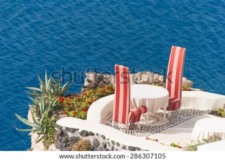 Cafe on the terrace with a beautiful sea view, Santorini island, Greece - stock photo