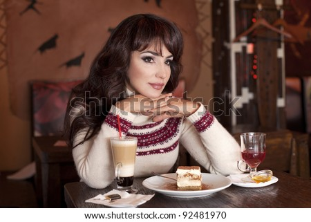 Cafe Pretty boring missing woman sitting in cafe restaurant with a cup of tea coffee cocktail eating tasty dessert  cheesecake tiramisu - stock photo