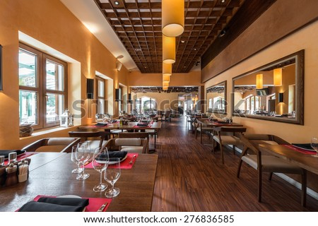 Cafe restaurant interior with wooden furniture, lighting equipment and decoration. - stock photo