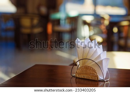 Cafe still life with paper napkins on dark wooden table - stock photo
