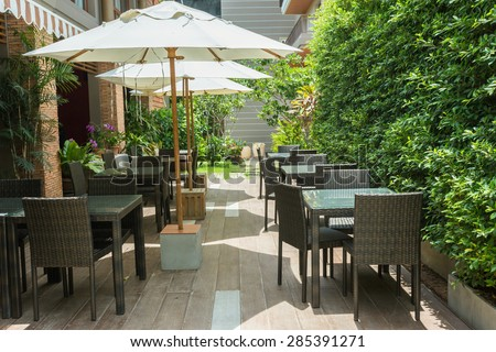 Cafe tables and chairs outside with big white umbrella and plant - stock photo