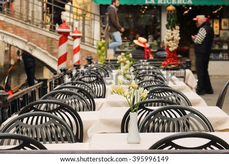 Cafe tables, covered with white tablecloths with devices on a background of the bridge and gondoliers. Venice Italy