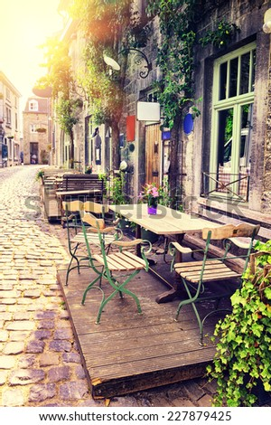 Cafe terrace in small European city at sunny summer day  - stock photo