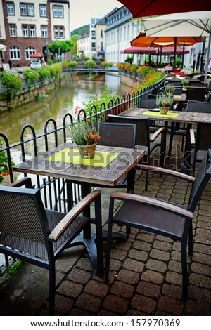 Cafe terrace on riverside in small European town - stock photo