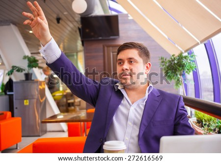 Cafe visitor raised his hand and invites waiter - stock photo
