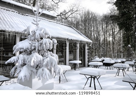 Cafe with snow. Winter landscaper. Garden furniture melting after a snowstorm.