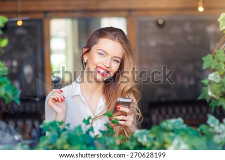 Cafe with wifi. Young attractive long hair woman using smart phone while sitting at restaurant. - stock photo