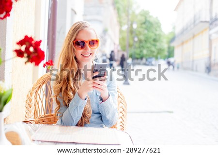 Cafe with wifi. Young attractive smiling woman using smart phone while sitting at sidewalk restaurant. - stock photo