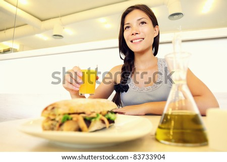 Cafe woman eating sandwich and drinking juice. Cute young asian woman. - stock photo