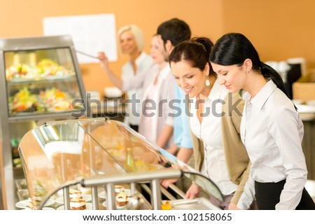 Cafeteria lunch two office colleagues woman choose food dessert self-service - stock photo