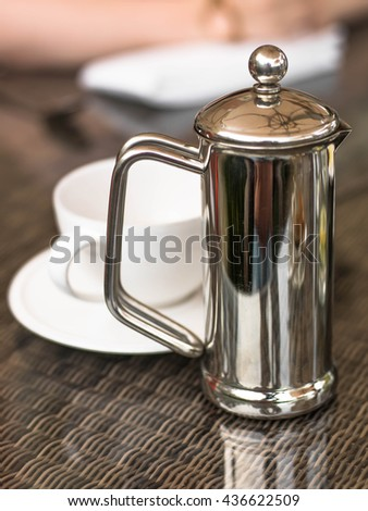 Cafetiere of Hot Coffee With a White Coffee Cup and Saucer On A Wicker Table - stock photo