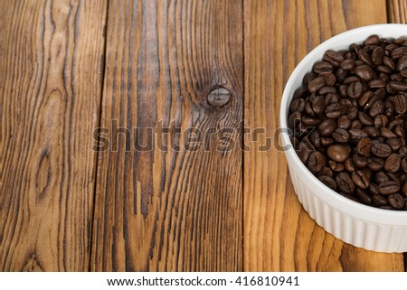 Caffeine. Cropped shot of aromatic coffee beans in a bowl on a wooden table copyspace on the side. - stock photo