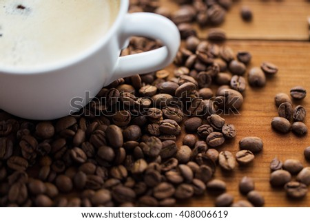 caffeine, objects and drinks concept - close up coffee cup and beans on wooden table - stock photo