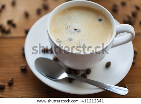 caffeine, objects and drinks concept - close up coffee cup and grains on wooden table - stock photo