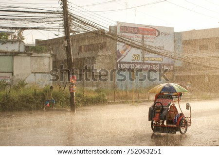 Cagayan de Oro, Philippines - May 25, 2009: Tricycle and a passerby during a heavy storm in Cagayan de Oro, Mindanao, Philippines