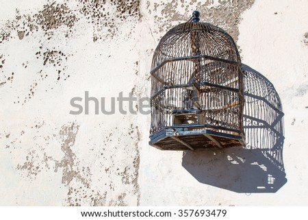 Cage on the wall Empty stylish bird cage hanging on the old wall.  - stock photo