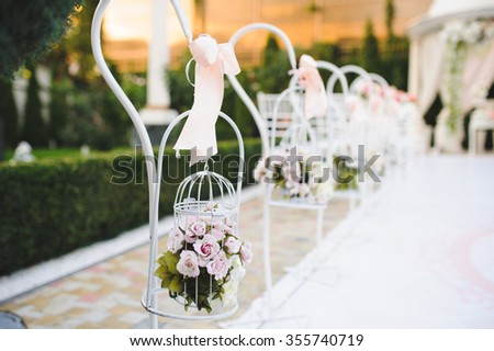 cage with roses hanging on stand