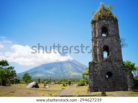 Cagsawa church ruins with the smoky Mount Mayon volcano in the background, Albay, Philippines. - stock photo