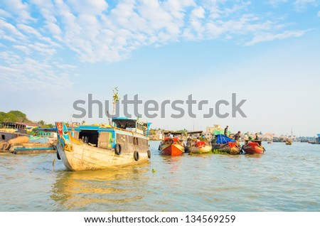 CAI BE TOWN, TIEN GIANG PROVINCE, VIETNAM - FEB 02: Unidentified traders on their boats at Cai Be Floating Market on February 02, 2013. Cai Be Market is one of most famous floating market in Vietnam. - stock photo
