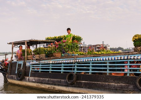 CAI BE TOWN, TIEN GIANG, VIETNAM - FEB 02, 2013: A family of flower vendors on their boats at Cai Be Floating Market in early morning. Cai Be Market is one of most famous floating market in Vietnam. - stock photo