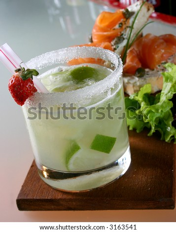 Caipirinha brazilian cocktail with appetizer - stock photo